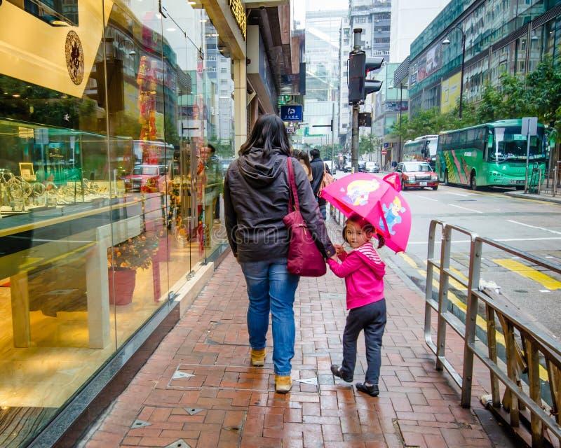 Una bambina con un ombrello rosa cammina lungo la via in Hong Kong con sua madre un giorno piovoso immagini stock libere da diritti