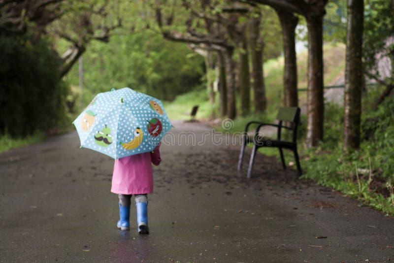 Una bambina con un ombrello variopinto immagini stock