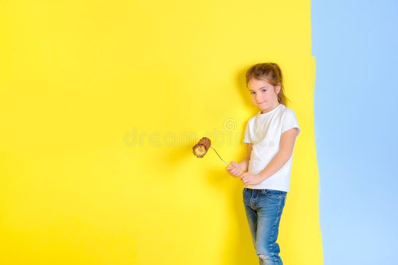 Una bambina con un rullo per la verniciatura in sue mani immagini stock