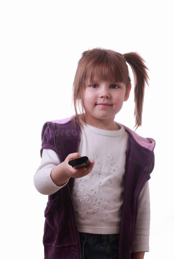 Una bambina con un'unità di telecomando fotografia stock