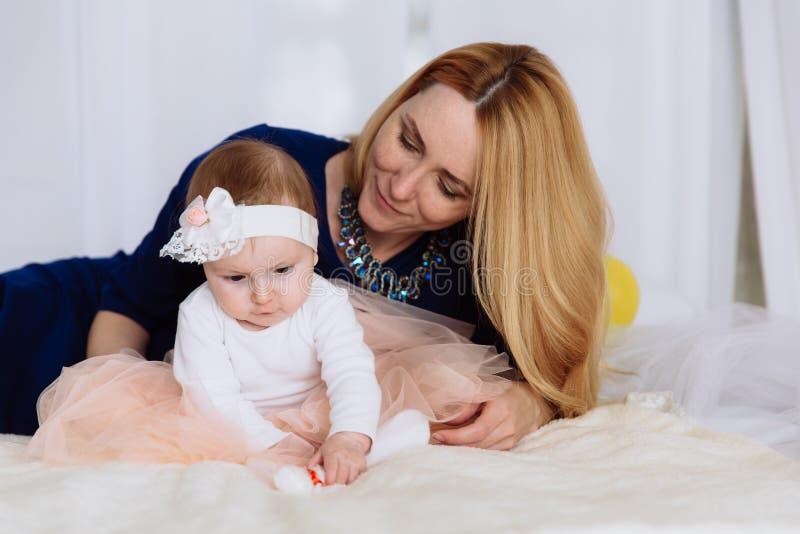 Una bambina del primo piano si siede sul provati e si concentra sul contatto della sua gamba Sua madre si siede da dietro e la gu immagine stock