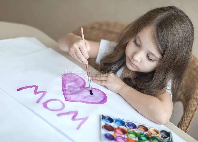 Una bambina dipinge un cuore su una cartolina d'auguri casalinga come regalo per il giorno di madre immagini stock