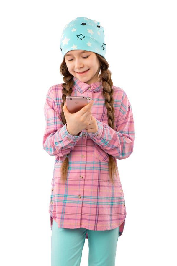 Una bambina dolce che gioca sul suo telefono cellulare isolato su fondo bianco fotografia stock libera da diritti