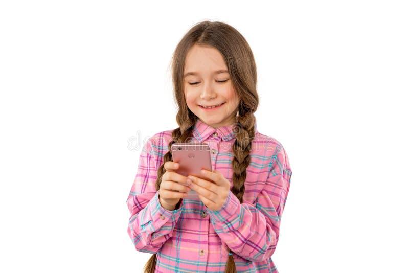Una bambina dolce che gioca sul suo telefono cellulare isolato su fondo bianco fotografie stock