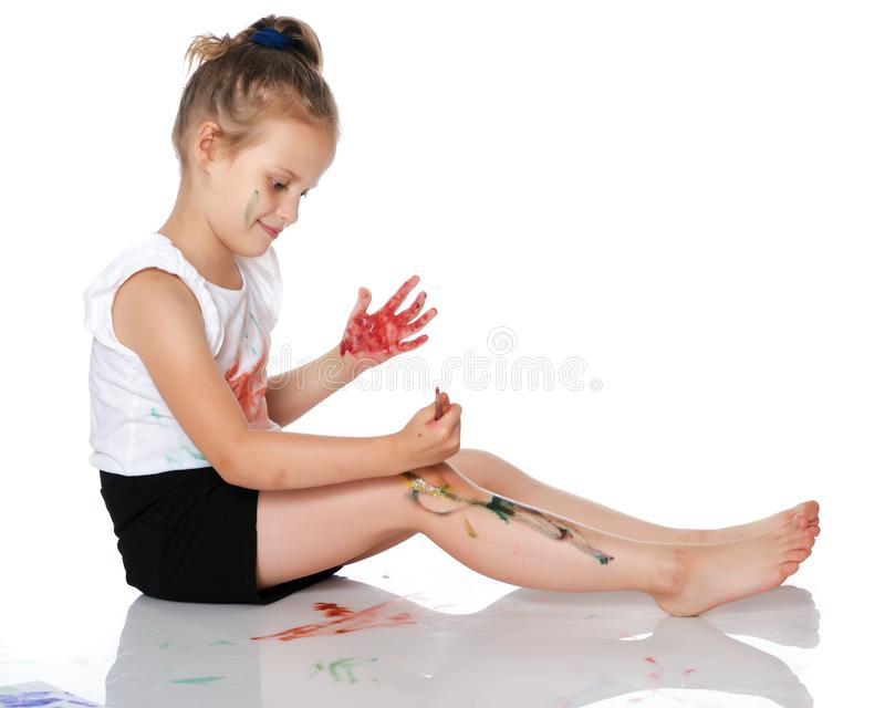 Una bambina estrae le pitture sul suo corpo fotografia stock