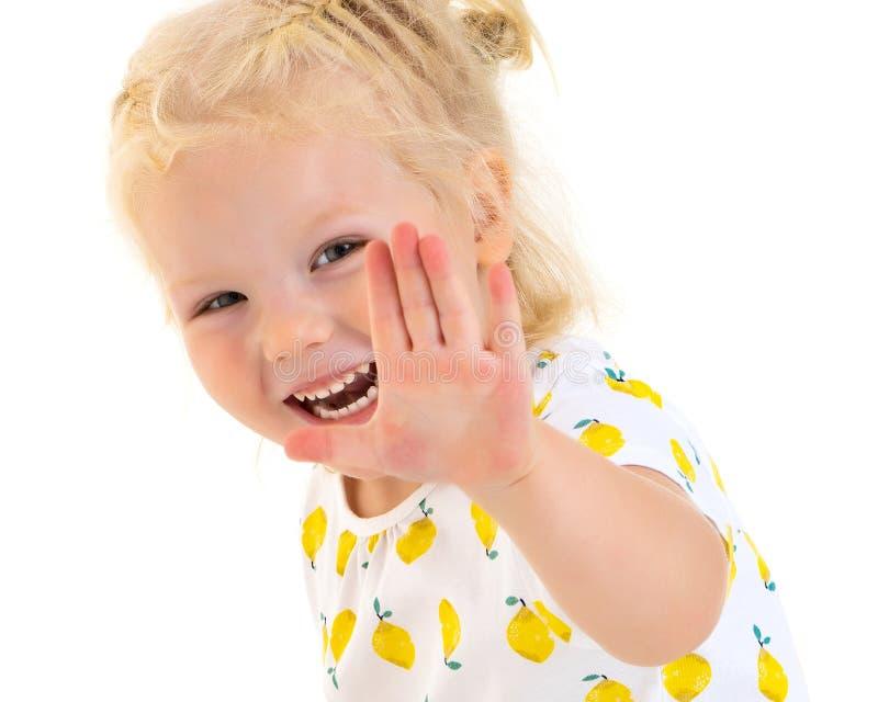 Una bambina felice sta ondeggiando la sua mano immagine stock