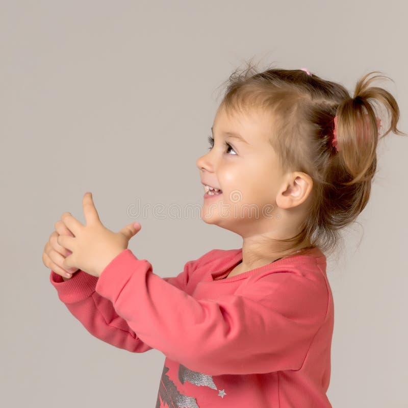 Una bambina felice sta ondeggiando la sua mano fotografie stock