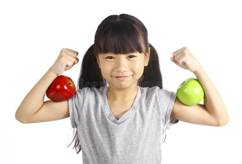 Una bambina flette il suo muscolo mentre ostenta la mela che ha fatto il suoi forte e sano fotografia stock
