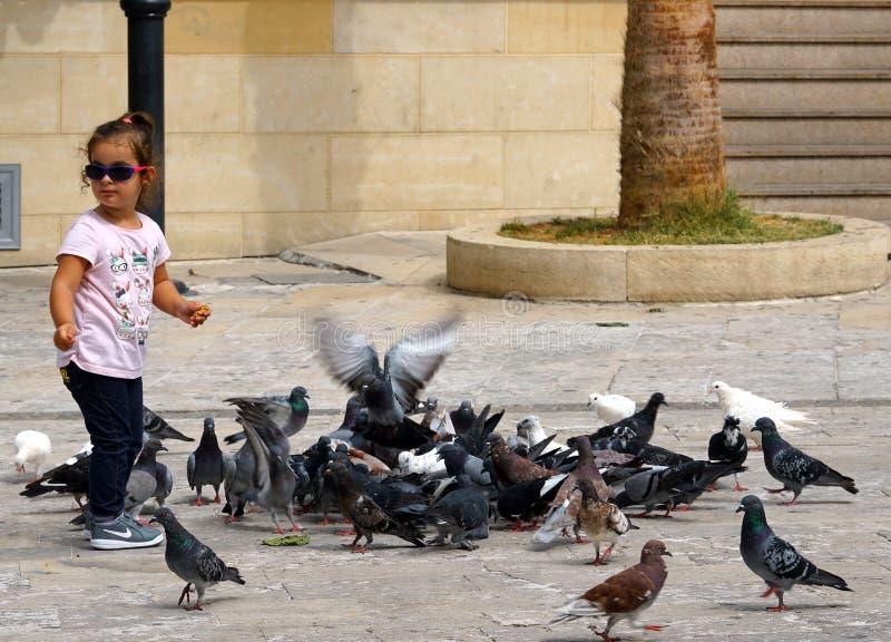 Una bambina gioca i piccioni d'alimentazione a Candia immagine stock libera da diritti