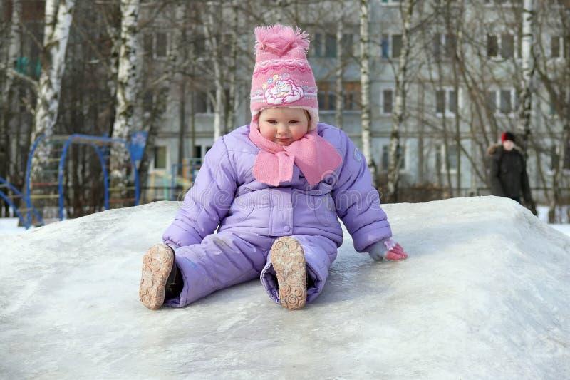 Una bambina ha rotolato giù lo scorrevole del ghiaccio fotografia stock