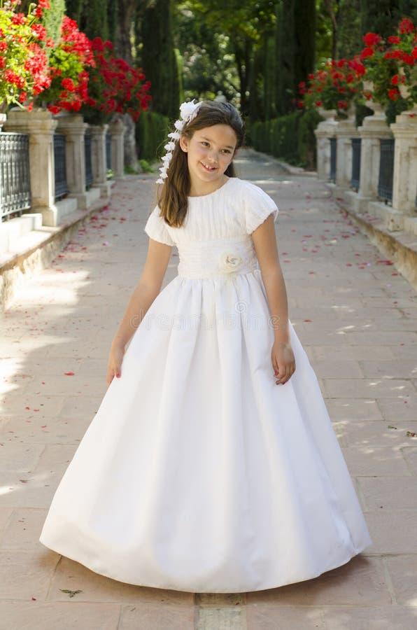 Una bambina indossa un bel vestito bianco per prendere la sua prima comunione fotografia stock libera da diritti