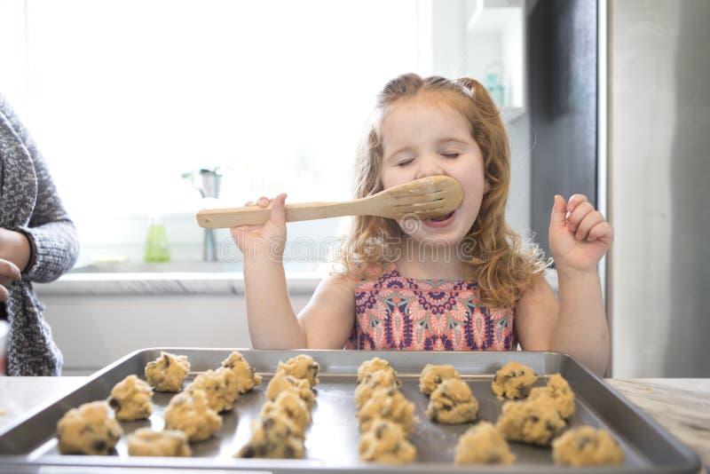 Una bambina lecca il cucchiaio mentre cuoce fotografia stock