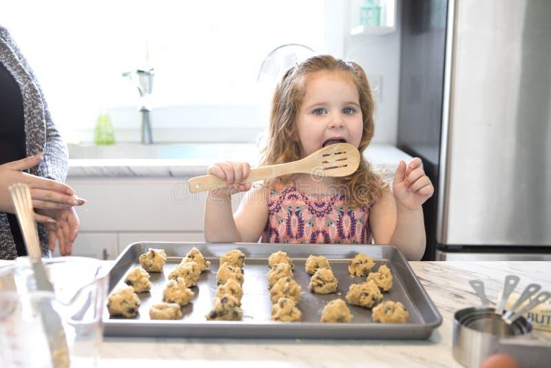 Una bambina lecca il cucchiaio mentre cuoce immagini stock libere da diritti