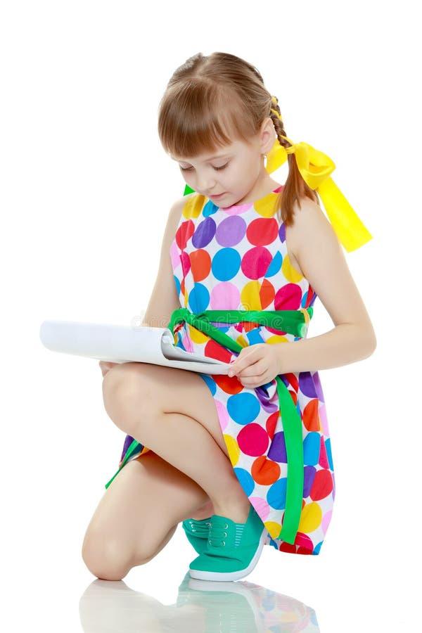 Una bambina legge il libretto fotografia stock libera da diritti