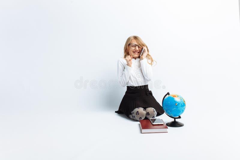 Una bambina, nell'immagine di un insegnante, i vetri d'uso con un globo ed i libri, parlando sul telefono e l'esultanza e la risa immagini stock