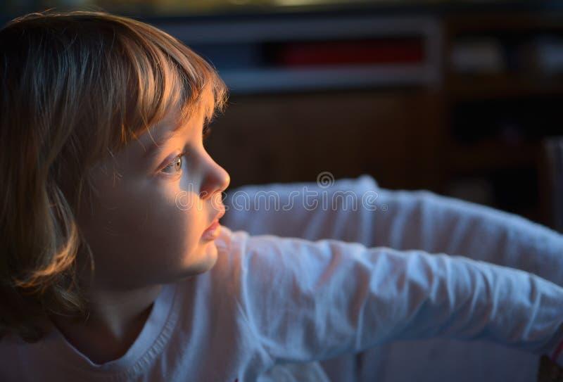 Una bambina osserva fuori la finestra il tramonto immagini stock