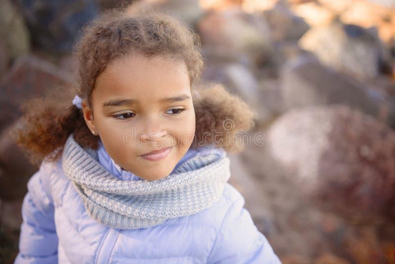 Una bambina, portando un cappello e presta a piedi nudi un'occhiata del sole Viaggio con il concetto dei bambini immagini stock libere da diritti