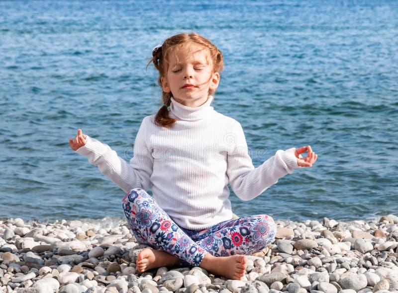 Una bambina pratica l'yoga e medita nella posizione di loto sul Pebble Beach immagine stock libera da diritti