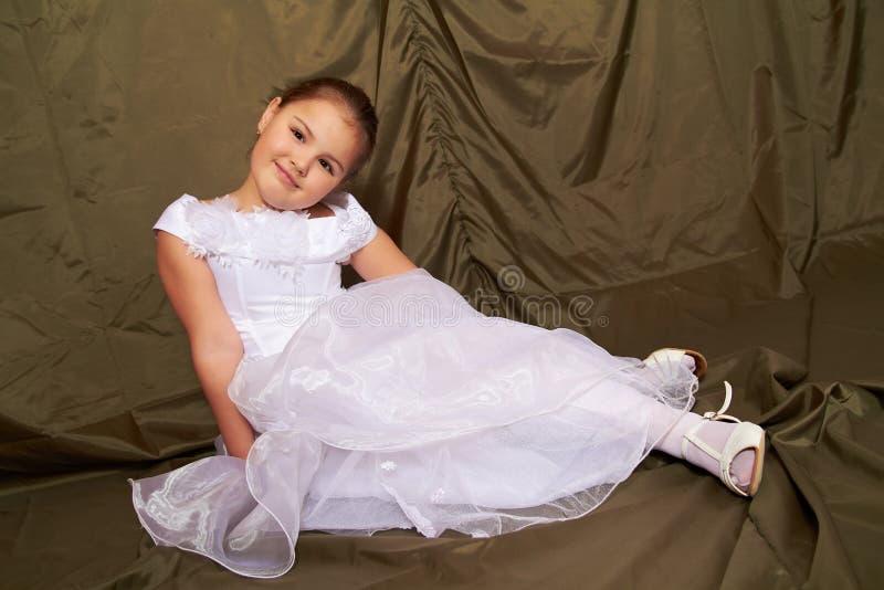 Una bambina si siede pensively. fotografie stock