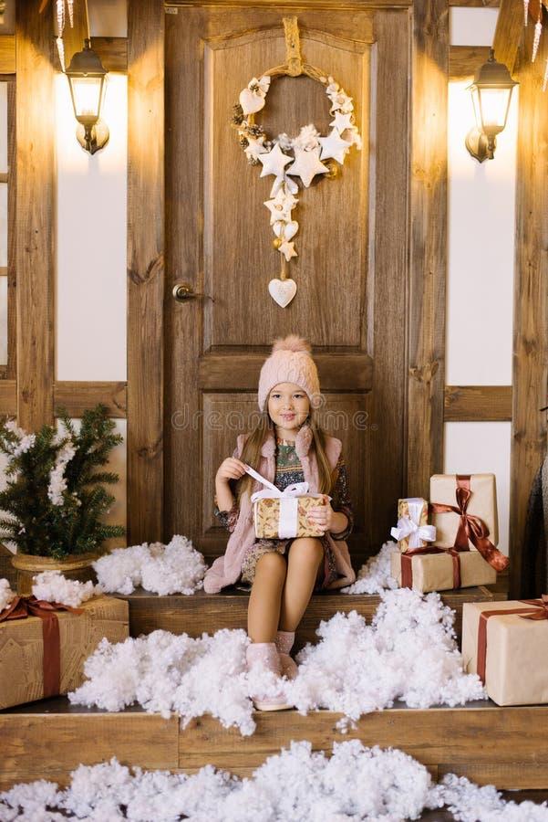 Una bambina siede sul portico di una casa decorata per Natale e Capodanno Lei tiene in mano una scatola regalo, la apre accanto immagini stock libere da diritti