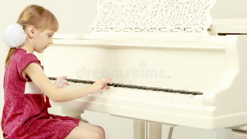 Una bambina sta sedendosi davanti ad un pianoforte a coda bianco immagine stock