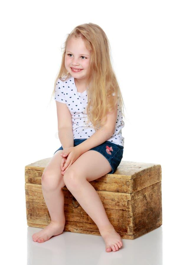 Una bambina sta sedendosi su una scatola di legno immagini stock