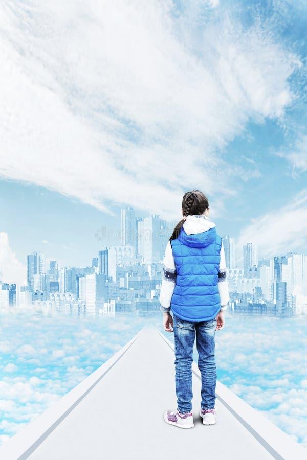 Una bambina sta sul modo ad una città mistica nel cielo fra le nuvole fotografie stock