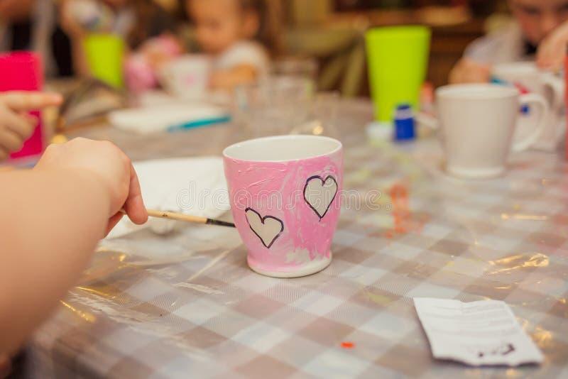 Una bambina sta tenendo una spazzola in sue mani e sta decorando la corrente alternata immagine stock libera da diritti