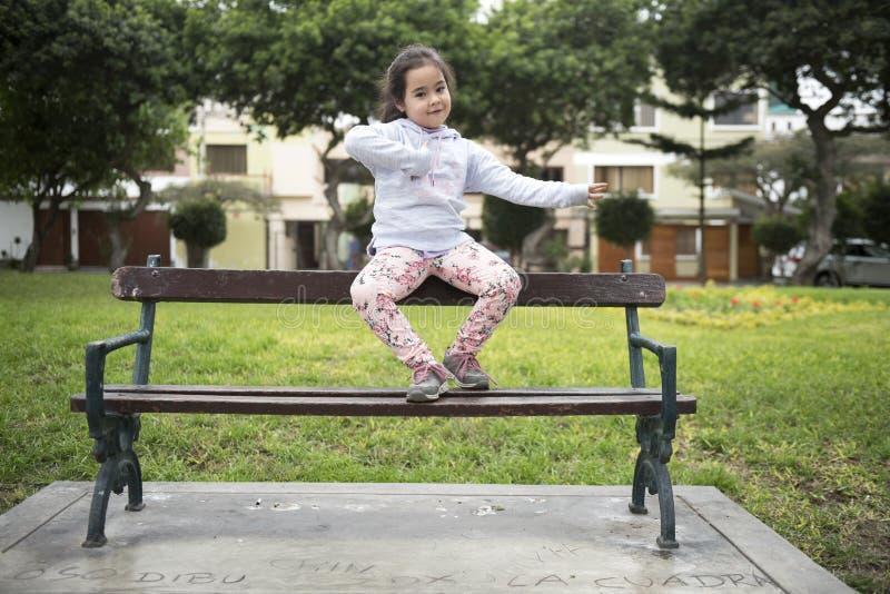 Una bambina sveglia di -5 anni che si siedono sul banco in un parco fotografie stock libere da diritti