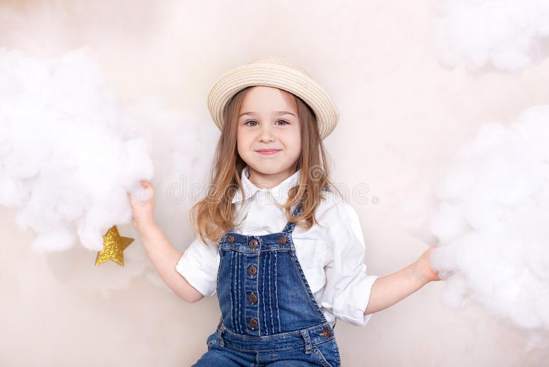 Una bambina sveglia sorridente vola nel cielo con le nuvole e le stelle Viaggiatore piccolo di Little dell'astrologo Il concetto  fotografia stock libera da diritti