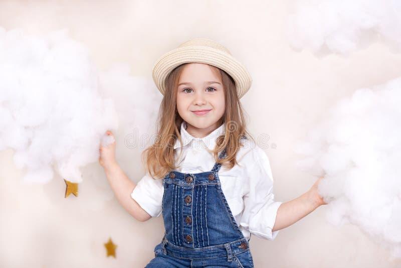 Una bambina sveglia sorridente vola nel cielo con le nuvole e le stelle Viaggiatore piccolo di Little dell'astrologo Il concetto  immagine stock libera da diritti