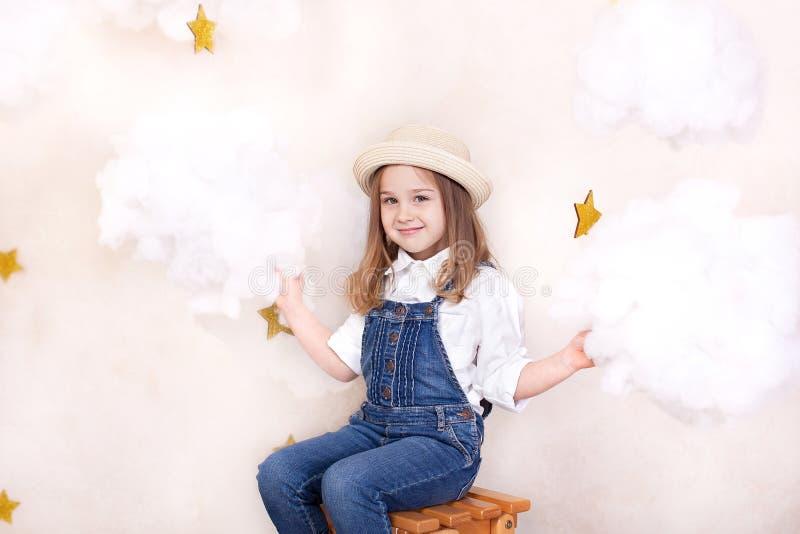 Una bambina sveglia sorridente vola nel cielo con le nuvole e le stelle Viaggiatore piccolo di Little dell'astrologo Il concetto  fotografia stock