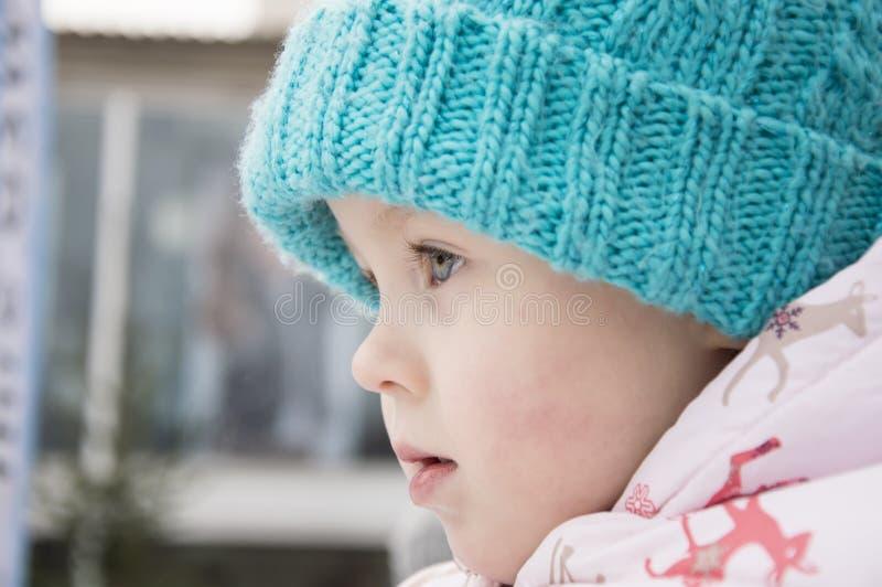 Una bambina sveglia in un primo piano blu caldo del cappello, fotografie stock
