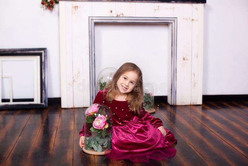 Una bambina sveglia in un vestito sta sedendosi sul pavimento con una rosa in una boccetta Esaminando la macchina fotografica Inf fotografia stock libera da diritti