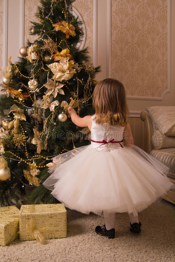 Una bambina in un vestito sontuoso si agghinda un albero di Natale fotografie stock libere da diritti