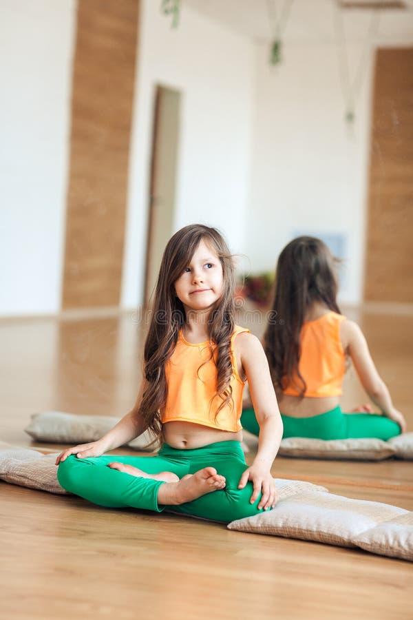 Una bambina in un'yoga di pratica della stanza luminosa, sedentesi su una coperta, spazzata da parte fotografia stock libera da diritti