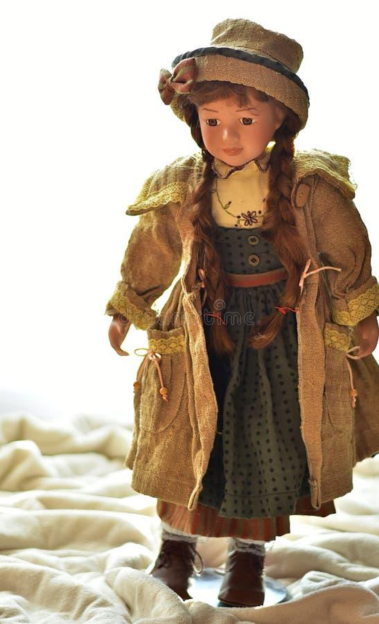 Una bambola della porcellana che sta su una piattaforma marrone fotografie stock libere da diritti