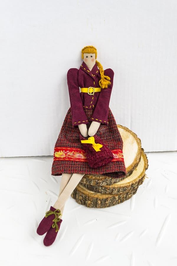 Una bambola femminile delle tilde in vestiti variopinti sta sedendosi in un canestro di vimini su un fondo bianco Registrazione d immagini stock