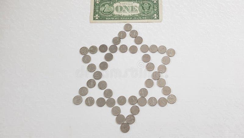 Una banconota americana del dollaro posta sopra le monete israeliane del metallo dello shekel sistemate in una forma dei sei punt immagine stock libera da diritti