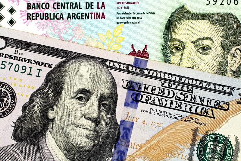 Una banconota da cinque pesi dall'Argentina con le cento banconote in dollari americana immagini stock libere da diritti