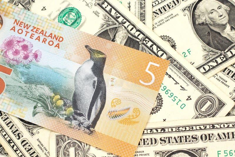 Una banconota del dollaro di Nuova Zelanda con le banconote in dollari degli Stati Uniti uno fotografia stock