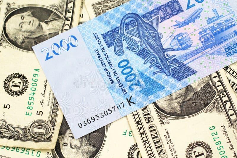 Una banconota dell'Africa Occidentale del franco con un fondo delle banconote in dollari degli Stati Uniti uno immagini stock