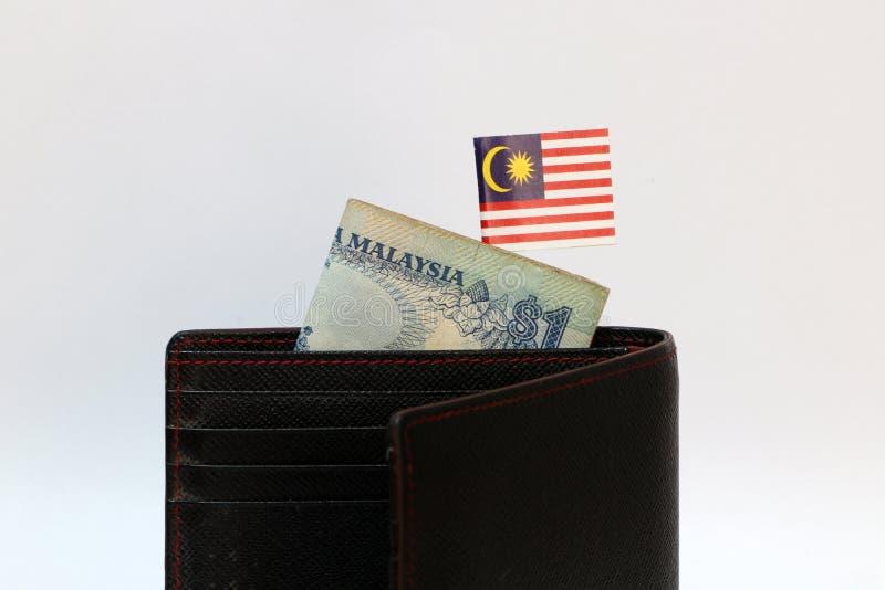 Una banconota di ringgit della Malesia e di mini bastone malese della bandiera di nazione sul portafoglio nero con fondo bianco immagini stock libere da diritti