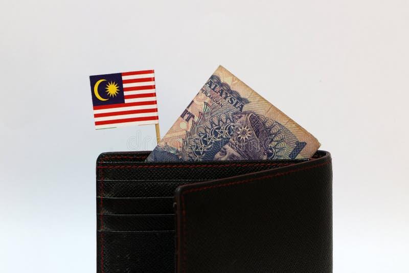 Una banconota di ringgit della Malesia e di mini bastone malese della bandiera di nazione sul portafoglio nero con fondo bianco fotografia stock