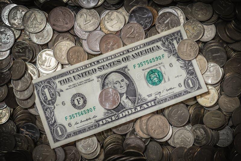 Una banconota in dollari è su tantissime monete russe delle denominazioni differenti fotografia stock