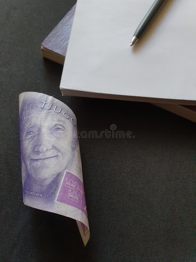 una banconota svedese di venti corone svedesi, dei libri e della penna nera fotografie stock libere da diritti
