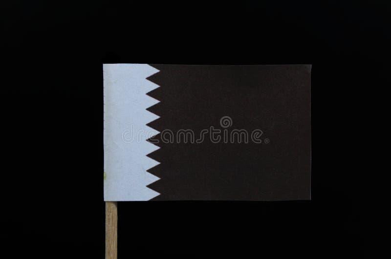 Una bandera única e interesante de Qatar en palillo en fondo negro Una banda blanca en el lado del alzamiento, separado de un áre imagenes de archivo