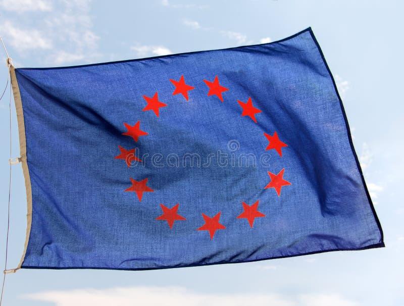 Una bandera azul con las estrellas rojas en alborotos de los círculos en el cielo imágenes de archivo libres de regalías