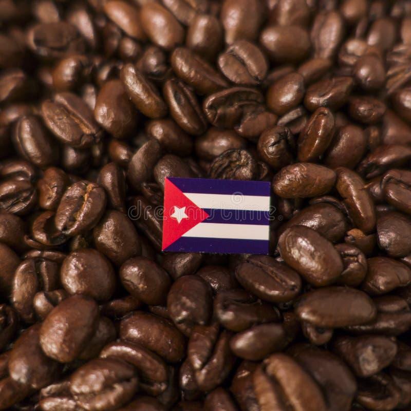Una bandera de Cuba colocada sobre los granos de café asados fotos de archivo libres de regalías