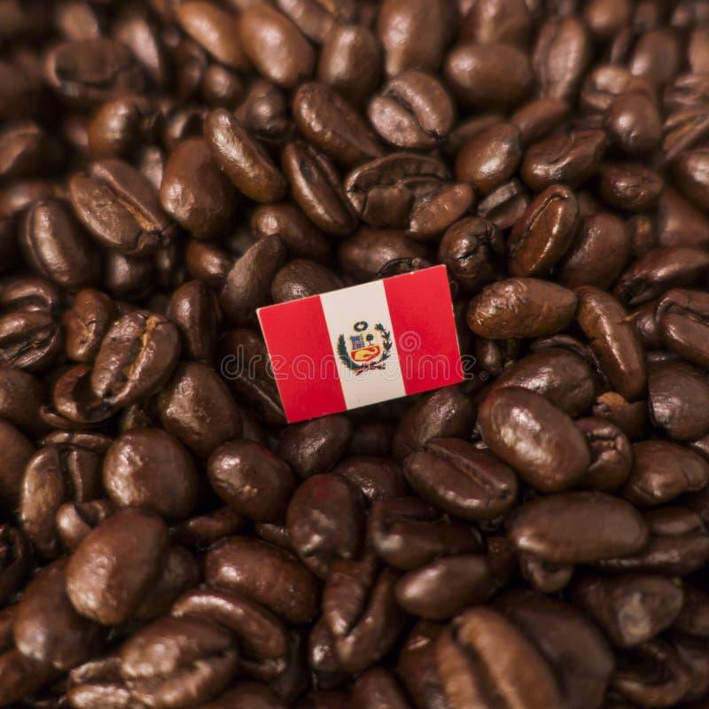 Una bandera de Perú colocada sobre los granos de café asados imagen de archivo